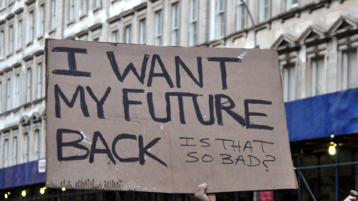 Cardboard sign: I Want my future back